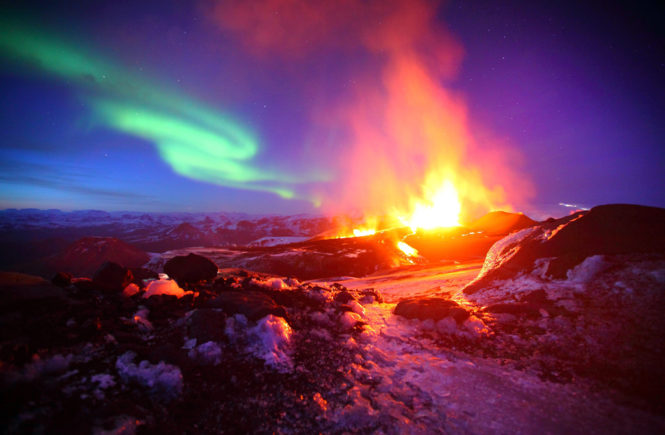 One of the incredible pictures taken by James Appliton before the Eyjafjallajˆkull volcano sent out it's huge ash cloud. See MASONS story MNVOLCANO;  These stunning pictures show the Northern Lights shining over erruptions at the troublesome Icelandic volcano whose ash cloud caused flight chaos across Europe. Purple and blue lights contrast with bright yellow and red lava as it flows from the Eyjafjallajˆkull volcano, which was erupting from beneath its ice cap. Freelance photographer James Appleton, 23, from Cambridge, risked his life trekking solo to the area and captured these incredible shots. The determined Cambridge University graduate spent five days observing the first phase of the eruption from a shack in nearby Fimmvˆruh·ls moutain pass. He decided to make the trip after seeing torrents of lava pouring down the mountain during the first fissure which erupted in March.   SWNS / Reporters